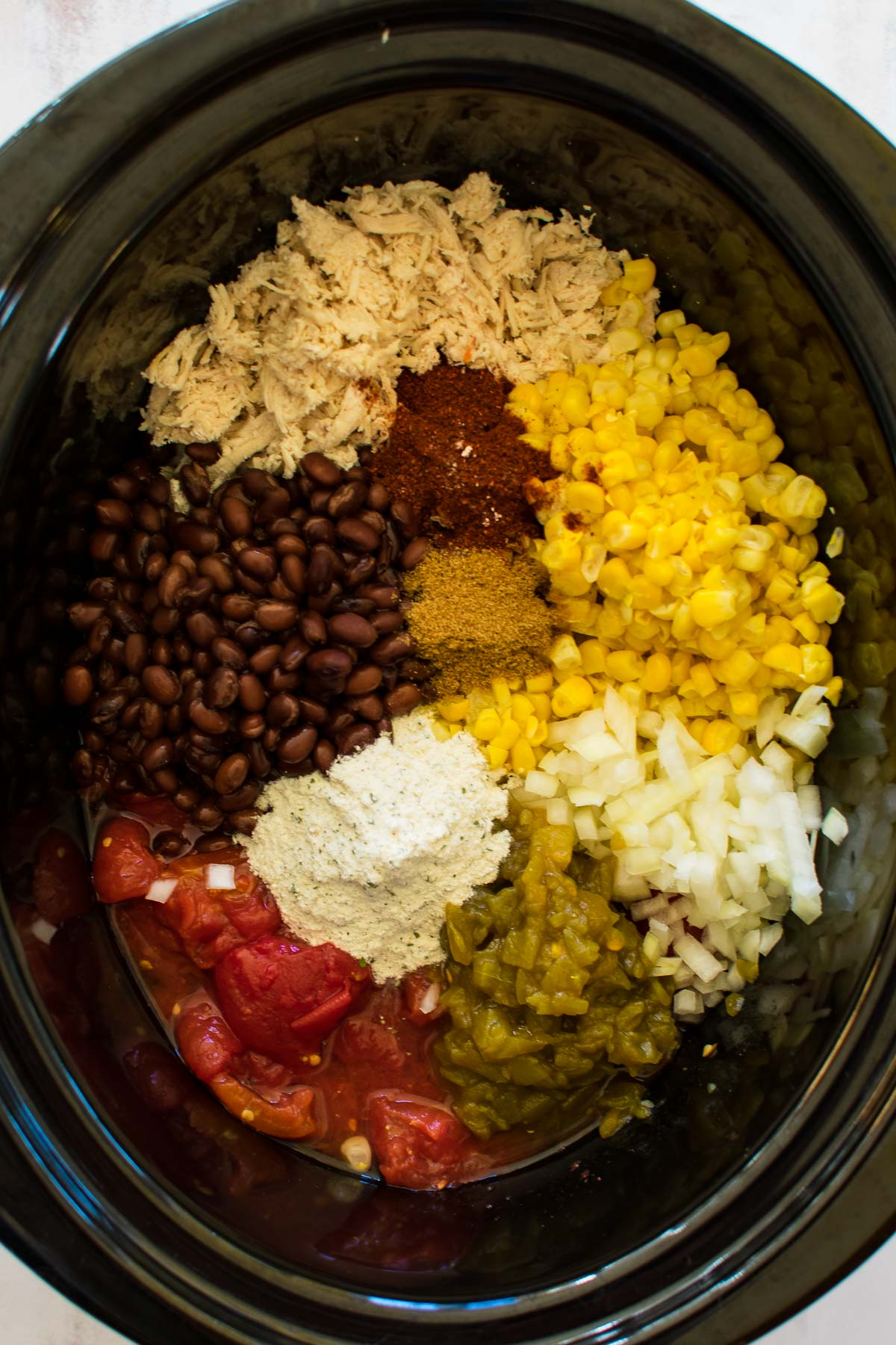 A slow cooker with corn, beans, onion, seasonings, tomatoes, and chilis.