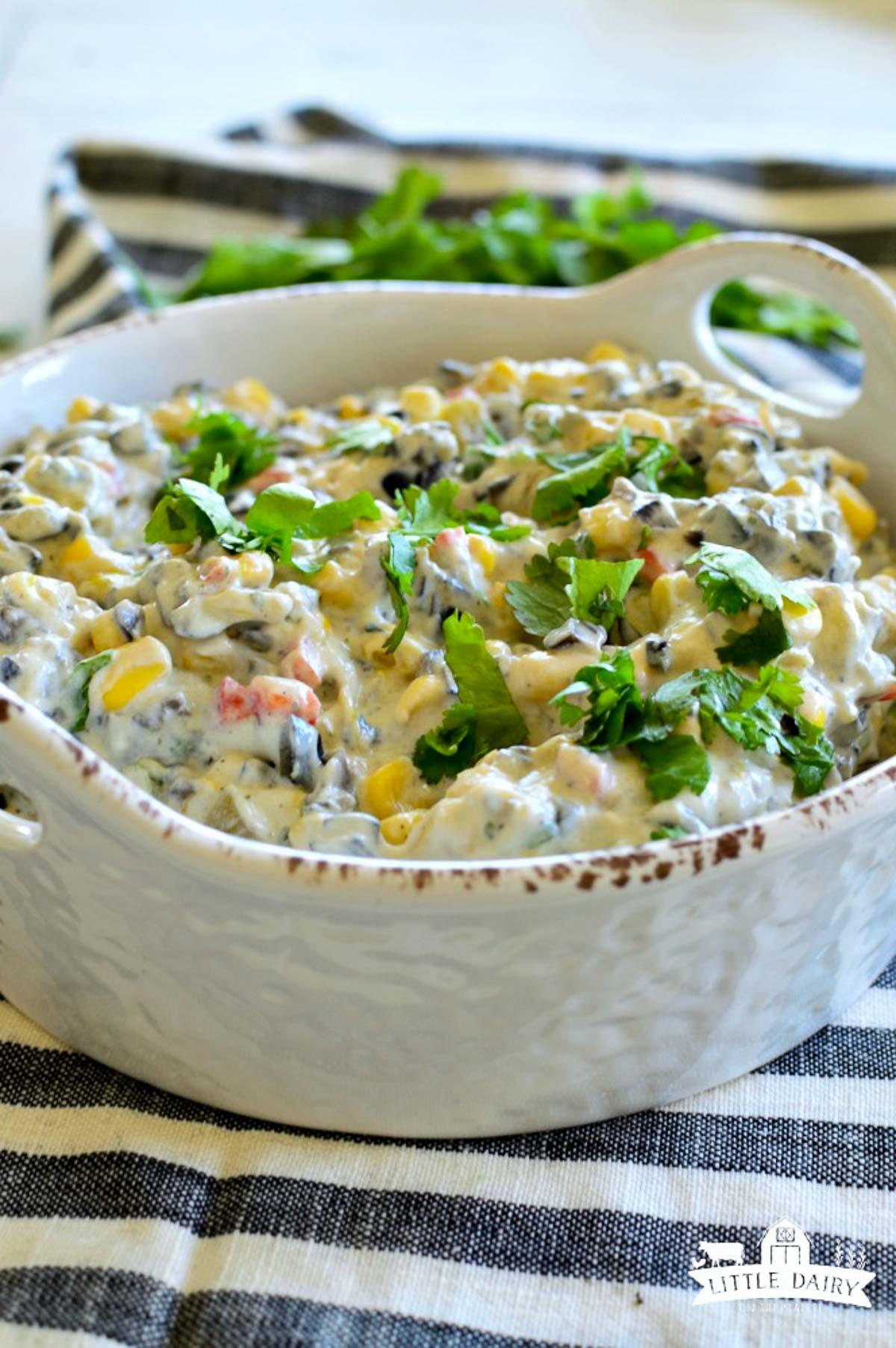 Veggie dip with fresh herbs on top of it.