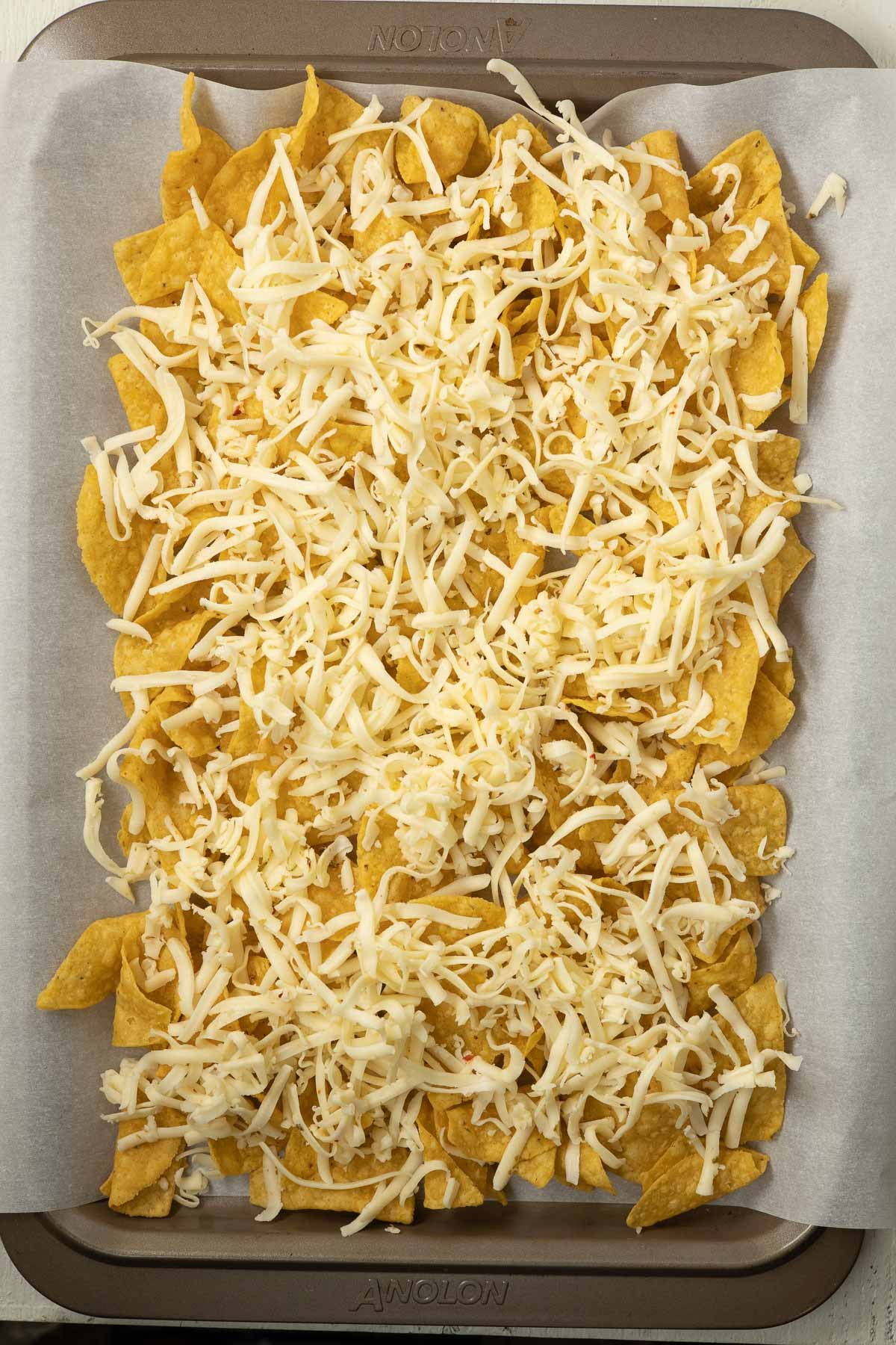 Sheet pan of tortilla chips topped with grated cheese.