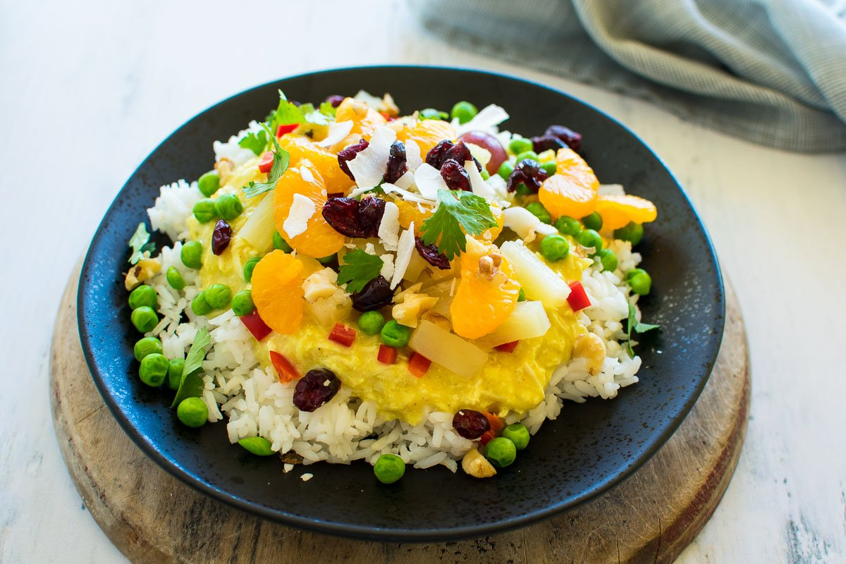 A plate with rice and Hawaiian haystacks gravy topped with vegetables and fruit.