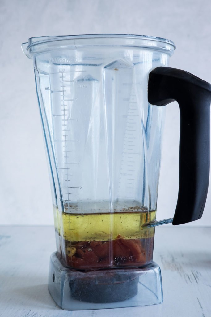 A blender with homemade salad dressing ingredients.