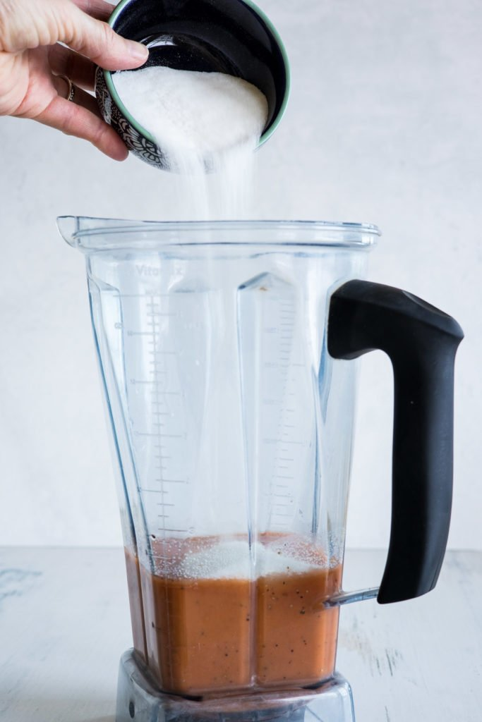 Sugar being poured into a blender with Catalina dressing in it.
