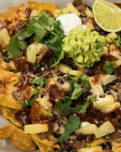 Baked nachos with tortilla chips and bbq pulled pork.