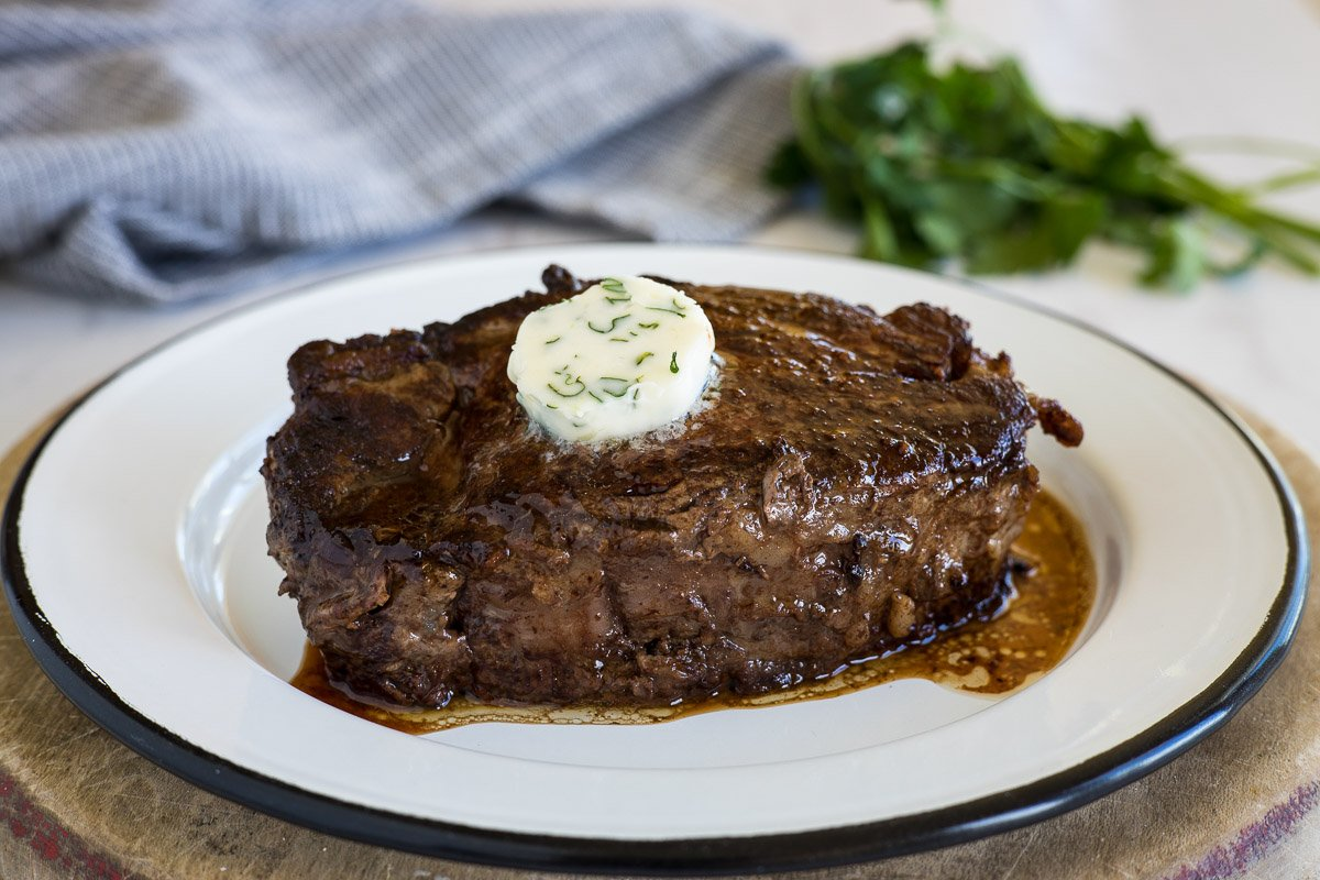 A skillet cooked beef tenderloin steak with butter and herbs on top.