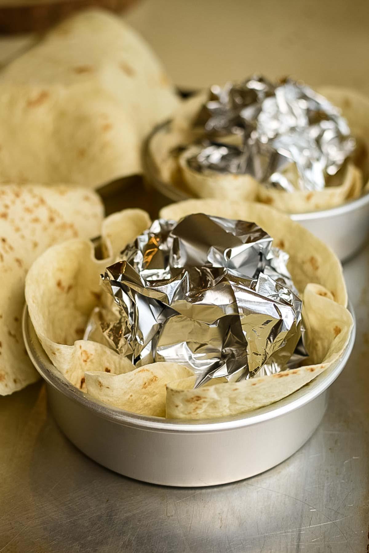 Tortilla shells in a bowl with aluminum foil.