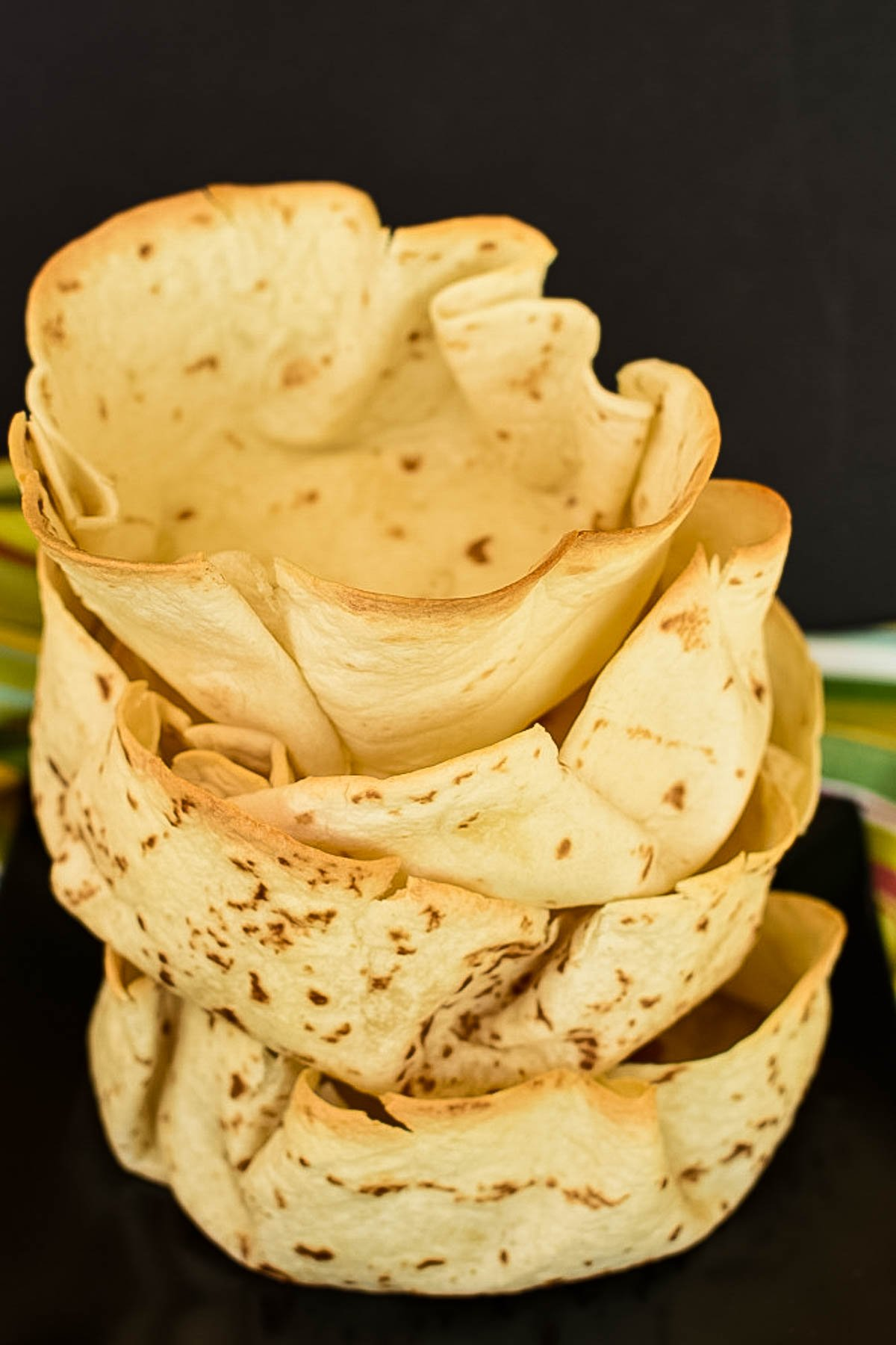 A stack of oven baked tortilla taco bowls.