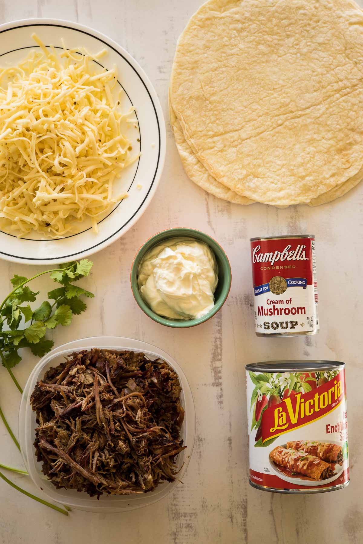 Ingredients needed to make enchiladas with shredded beef.