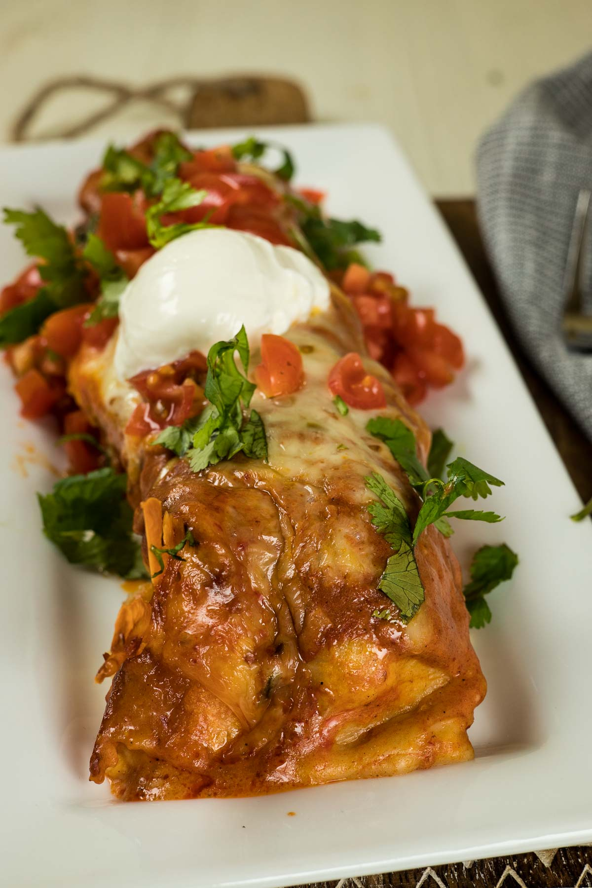 Beef enchilada with sour cream, tomatoes, and cilatnro.
