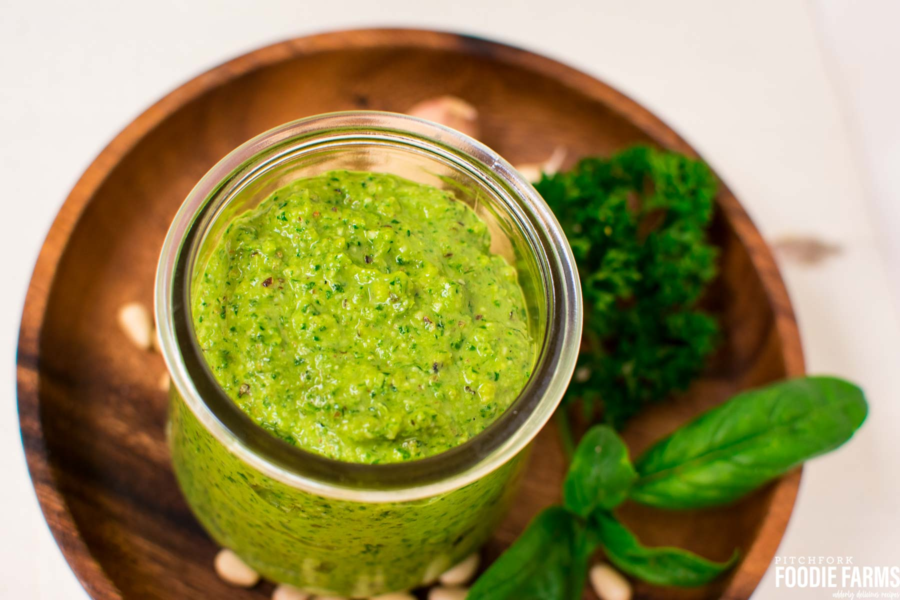 A jar of green pesto with fresh basil leaves, pine nuts and parsley sprinkled around it on a wooden plate.