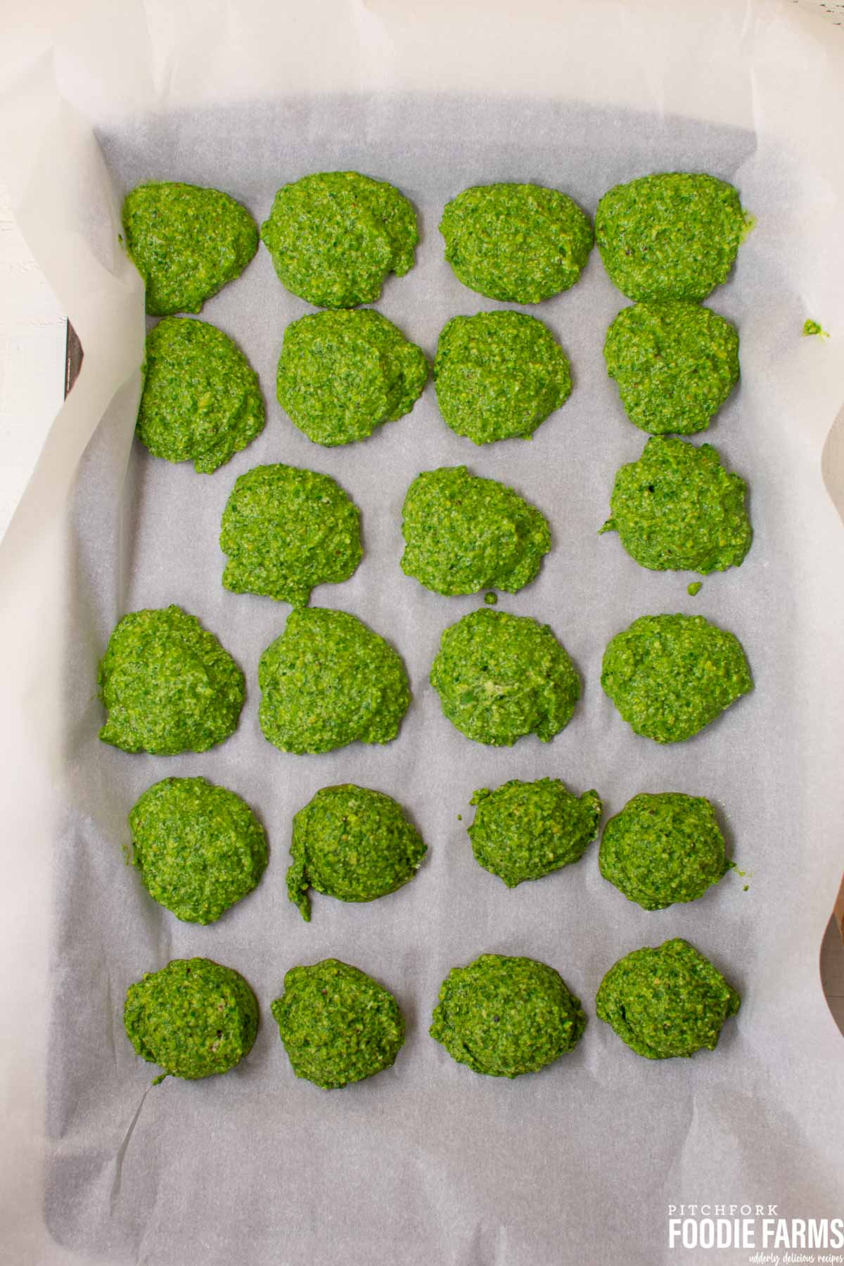 Scoops of pesto sauce on a parchment lined baking sheet.
