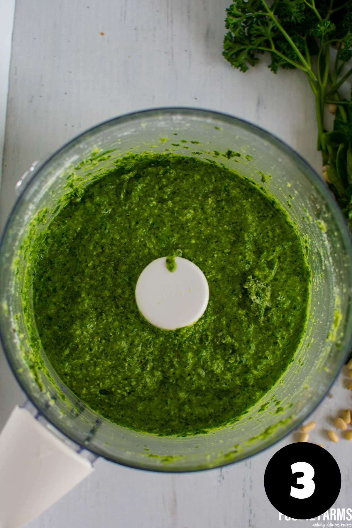 Blended pesto sauce in a food processor bowl.