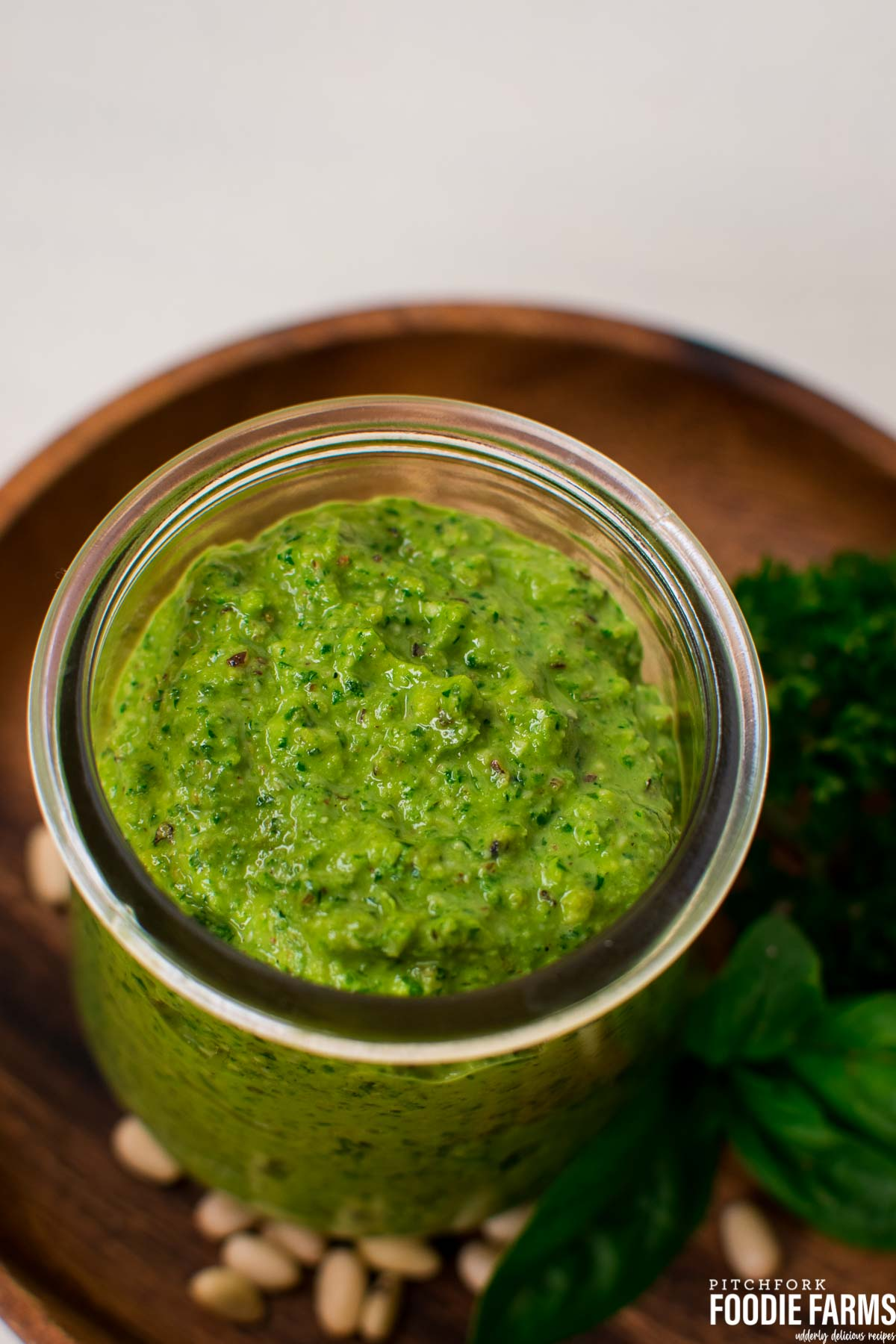 A glass jar with green pesto on a wooden plate.