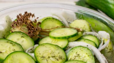 Cucumber salad in a glass bowl with dill.
