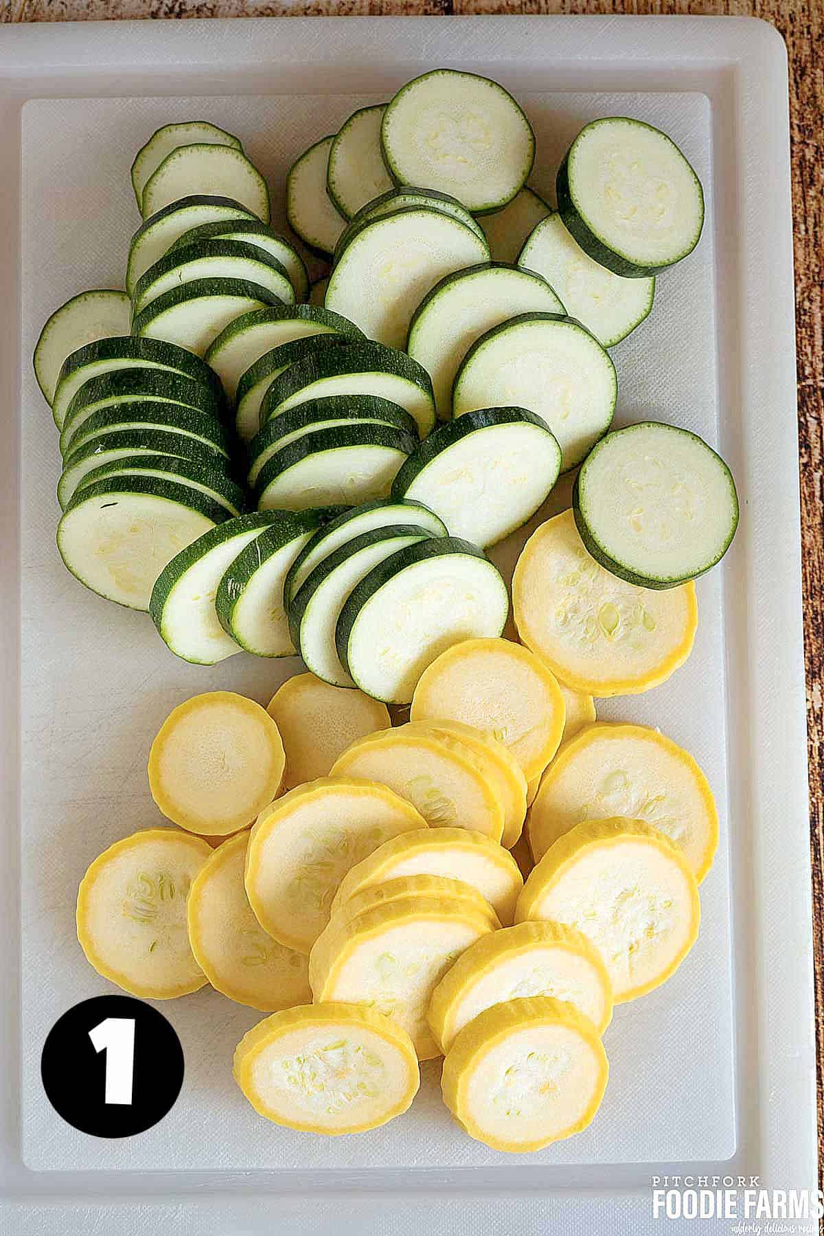 Sliced zucchini and yellow summer squash on a cutting board.