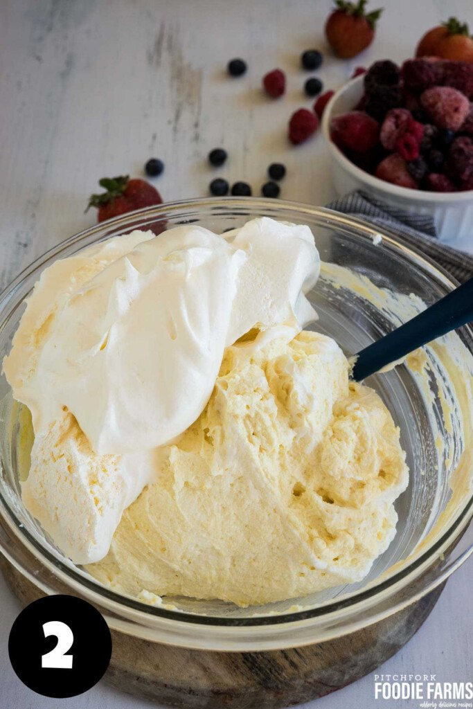 Vanilla pudding with whipped topping in a glass mixing bowl.