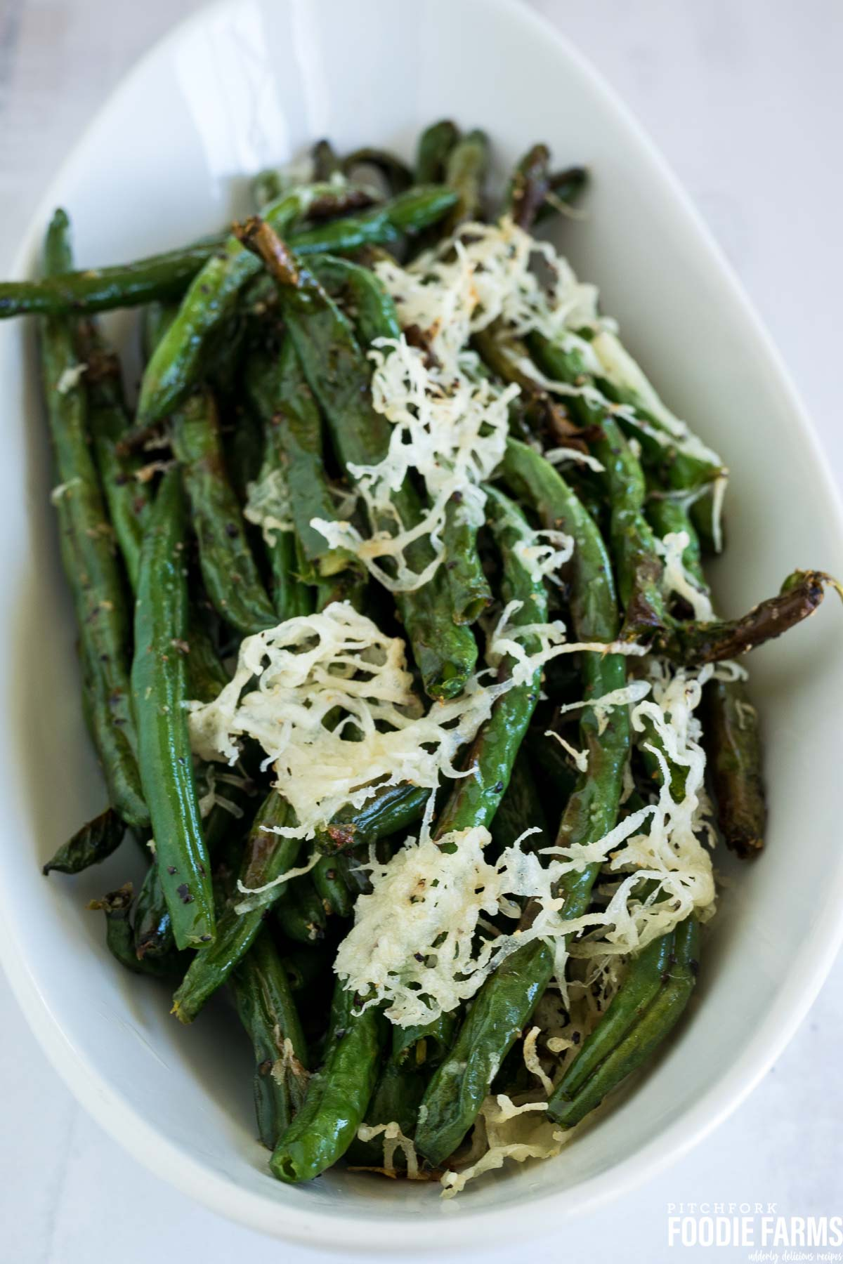 Oven baked green beans in a white serving dish with toasted parmesan cheese on top.