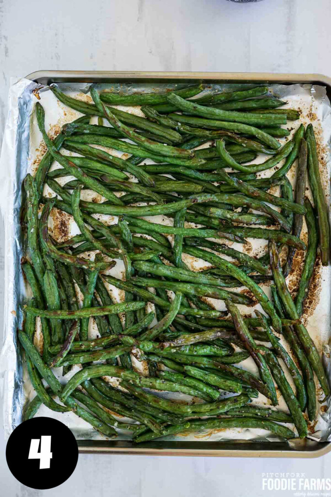 Roasted green beans on a baking sheet with browned bits.