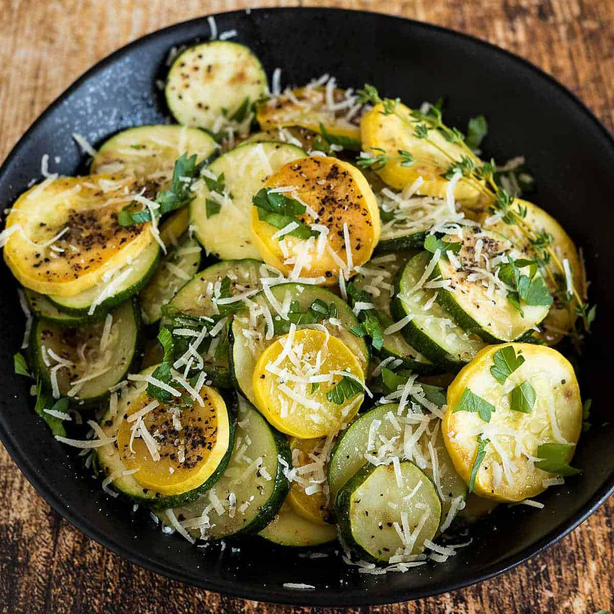 Zucchini and yellow squash cut into circles sprinkled with grated parmesan cheese and fresh parsley.