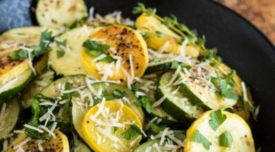 BBQ zucchini in a black bowl with parmesan and fresh parsley.