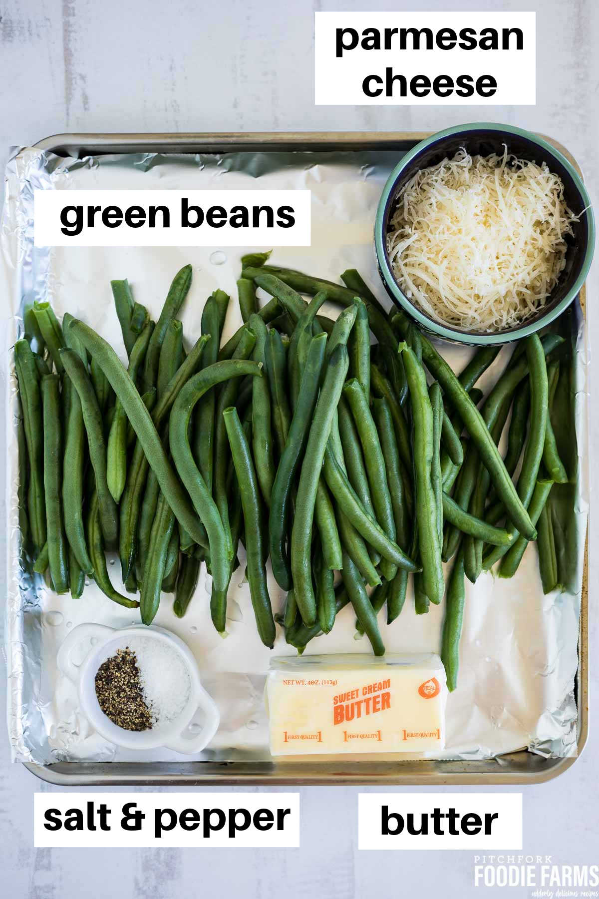 A sheet pan with fresh green beans, a cube of butter, salt and pepper, and grated parmesan cheese.