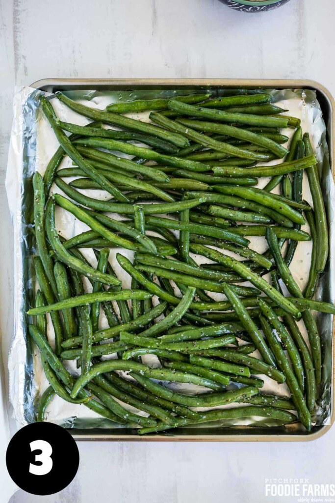 Raw green beans spread on a baking sheet.