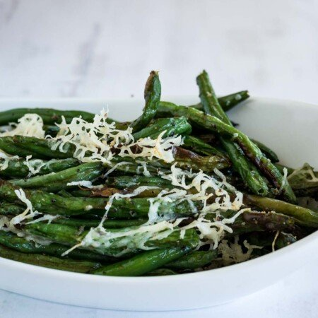 A white dish with green beans topped with shredded parmesan cheese.