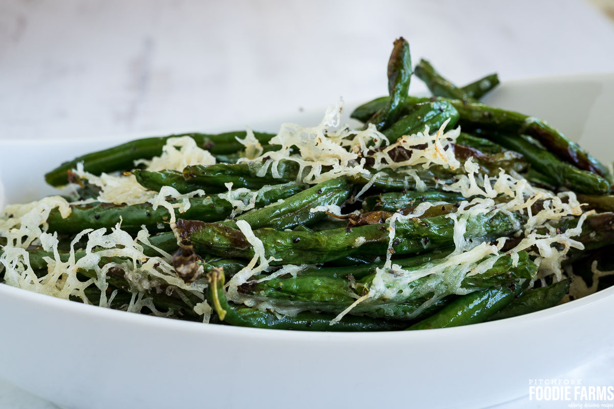 Cooked green beans in a white baking dish topped with grated cheese.