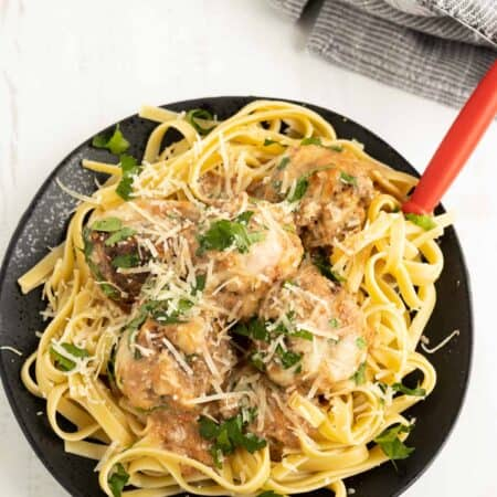 Pasta topped with meatballs in a creamy Italian tomato sauce sprinkled with cheese and herbs on a black plate.