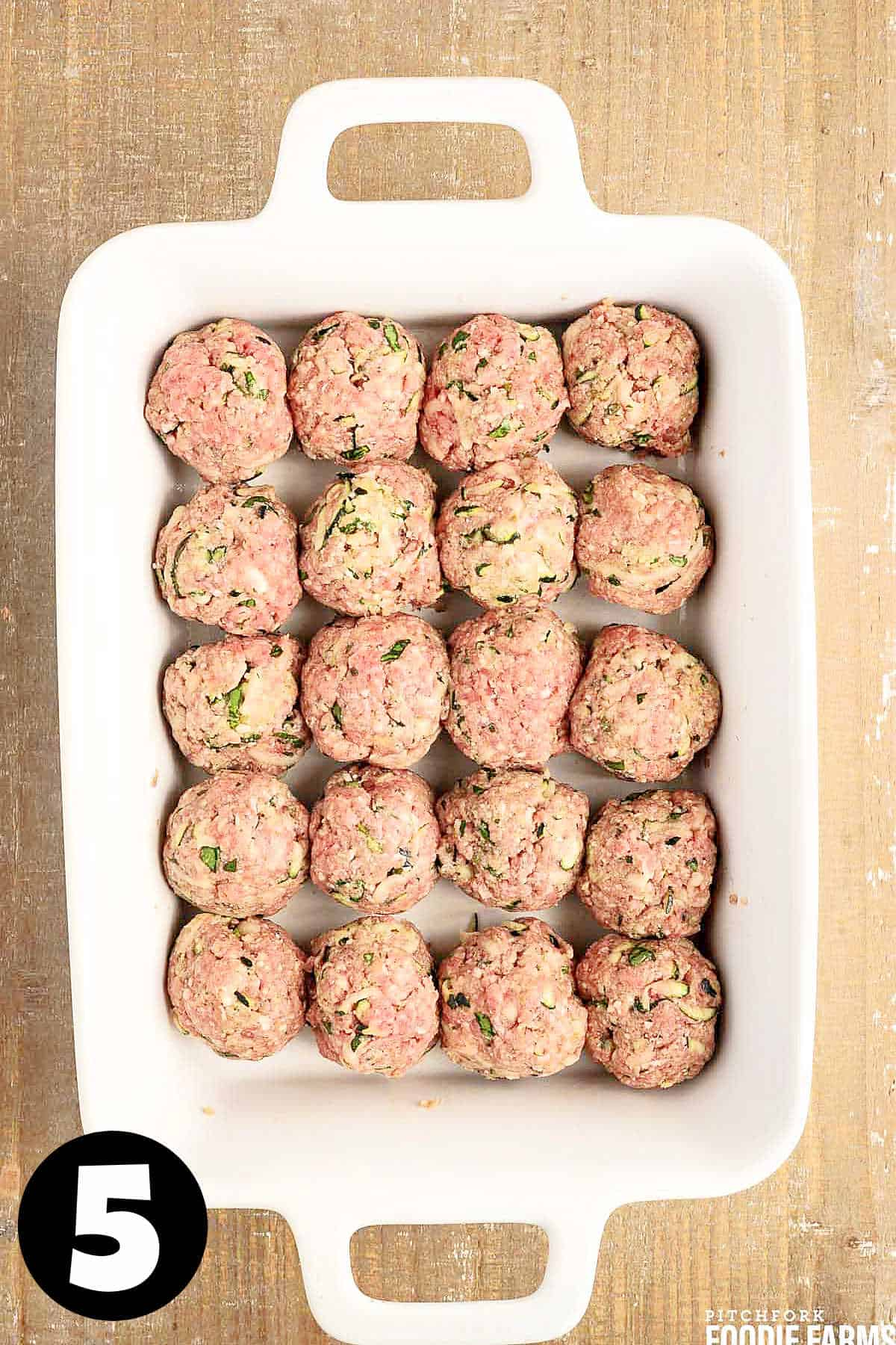 Raw meatballs in a white baking dish.