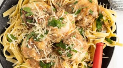 Meatballs made with beef and zucchini in a creamy tomato sauce serve over pasta.