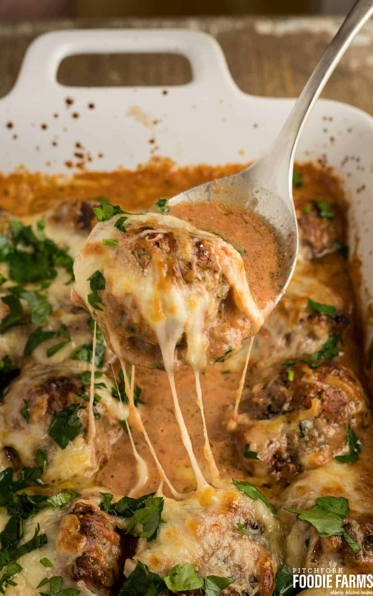 A cheesy meatball being lifted out of a white casserole dish on a spoon.