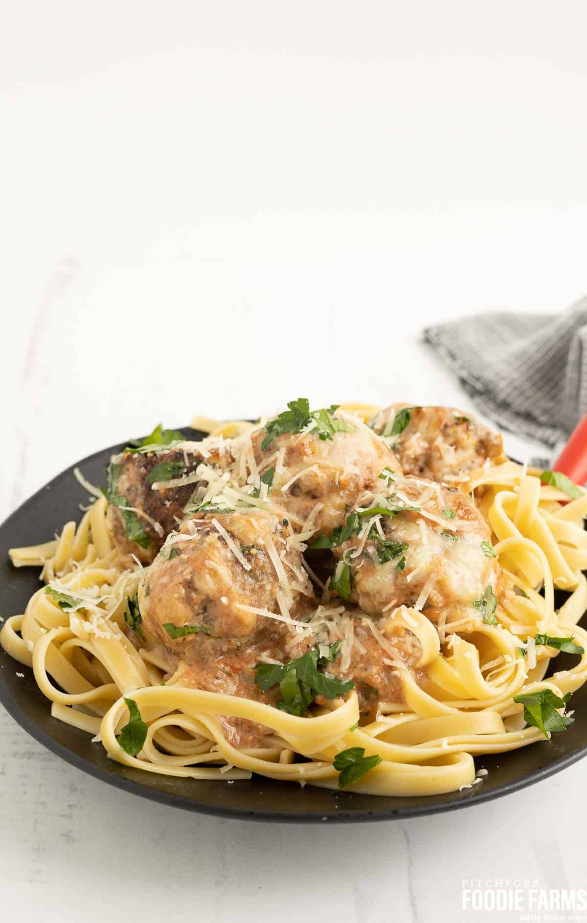 A black plate with zucchini meatballs on top of pasta with fresh herbs.