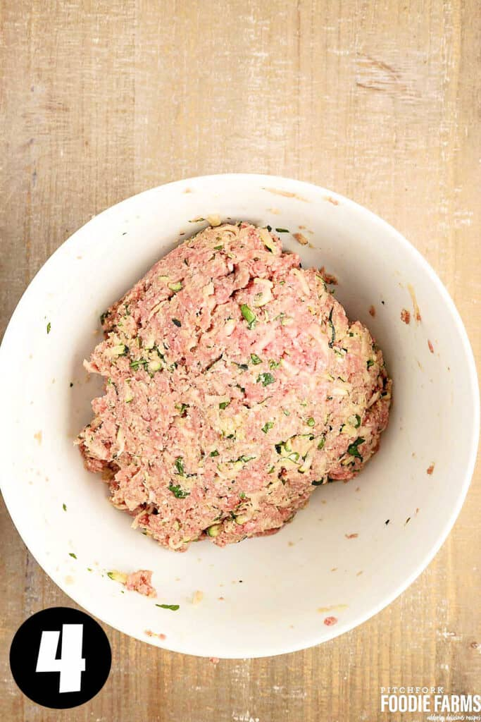 Ground beef mixed with herbs to make Italian meatballs with zucchini.