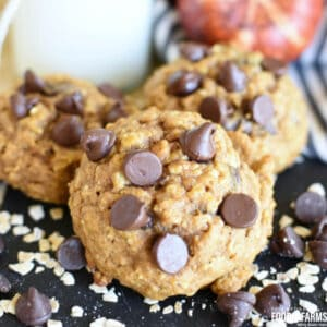 Pumpkin Oatmeal Chocolate Chip Cookies on a black napkin with oats and chocolate chips scattered around.