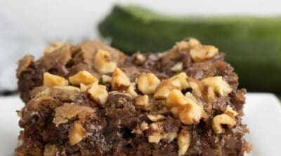 A piece of chocolate zucchini cake with walnuts and chocolate chips on top.