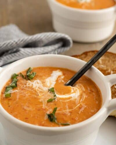 Tomato Soup with cream drizzled on top and fresh basil leaves